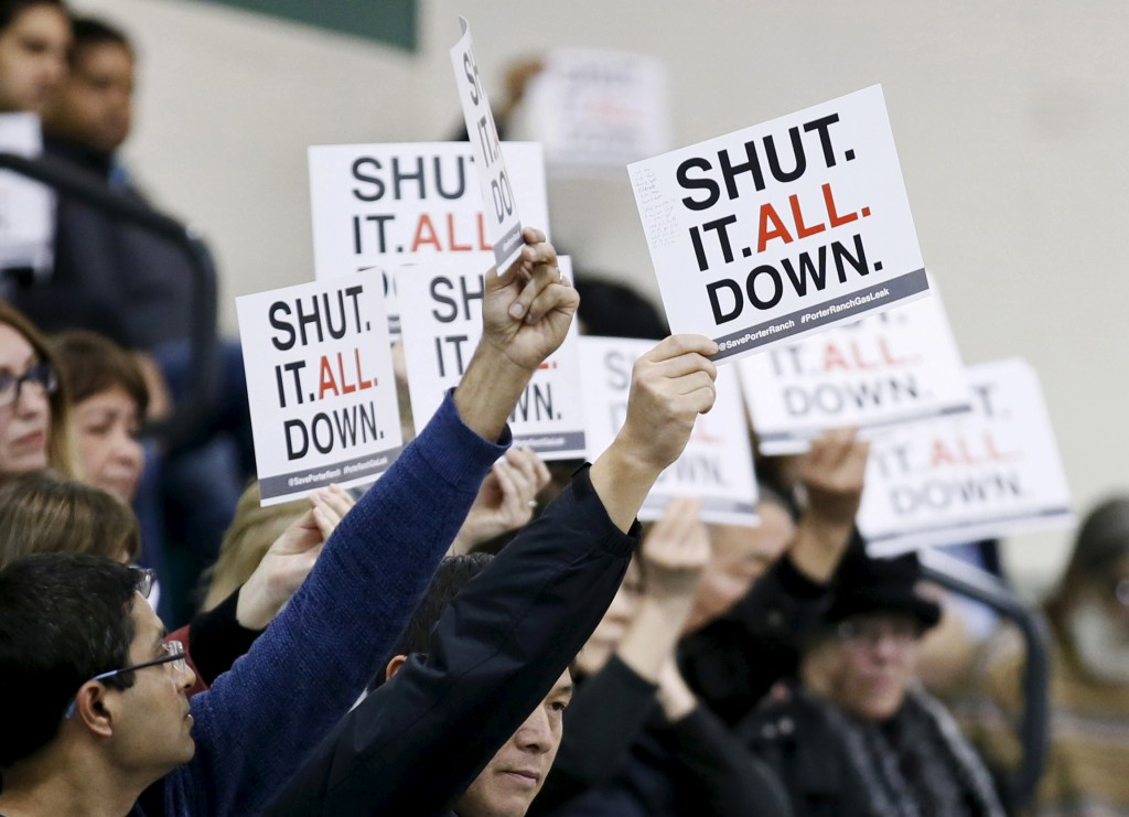 Residents of the Porter Ranch area of Los Angeles hold up signs related to a gas leak in their community during the meeting of the California Air Quality Management District in Granada Hills, California January 9, 2016. Photo by Danny Moloshok/REUTERS