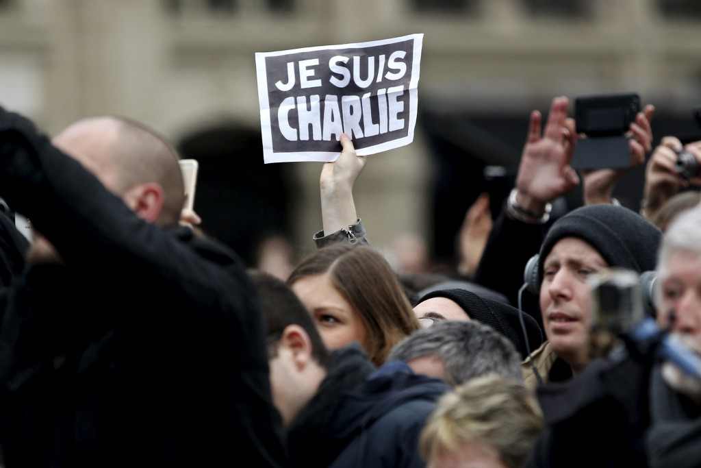 "A person holds up a ""Je Suis Charlie"" (I am Charlie) sign during a ceremony at Place de la Republique square to pay tribute to the victims of last year's shooting at the French satirical newspaper Charlie Hebdo, in Paris, France, January 10, 2016. France this week commemorates the victims of last year's Islamist militant attacks on satirical weekly Charlie Hebdo and a Jewish supermarket with eulogies, memorial plaques and another cartoon lampooning religion.  REUTERS/Yoan Valat/Pool - RTX21QA0"