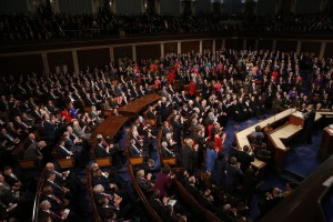 Democratic members of Congress rise to their feet for a standing ovation as Republican members remain seated during U.S. President Barack Obama's State of the Union address to a joint session of Congress in Washington, January 12, 2016. REUTERS/Jonathan Ernst - RTX224XG