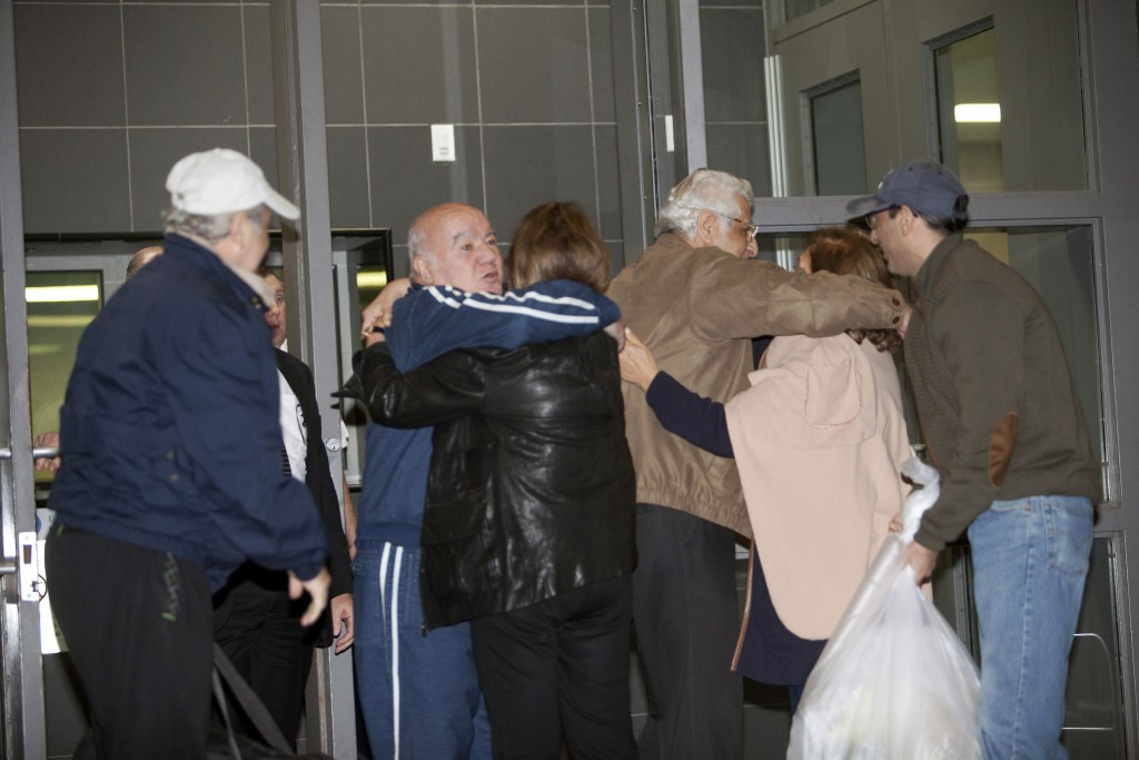 Family and friends embrace Bahram Mechanic (in the blue jump suit) and Khosrow Afghahi (in the tan jacket) at Federal Detention Center Houston, Texas Jan. 17, 2016. Several Iranian-Americans held in U.S. prisons after being charged or convicted for sanctions violations have been released under a prisoner swap.   REUTERS/Daniel Kramer      TPX IMAGES OF THE DAY      - RTX22QL1