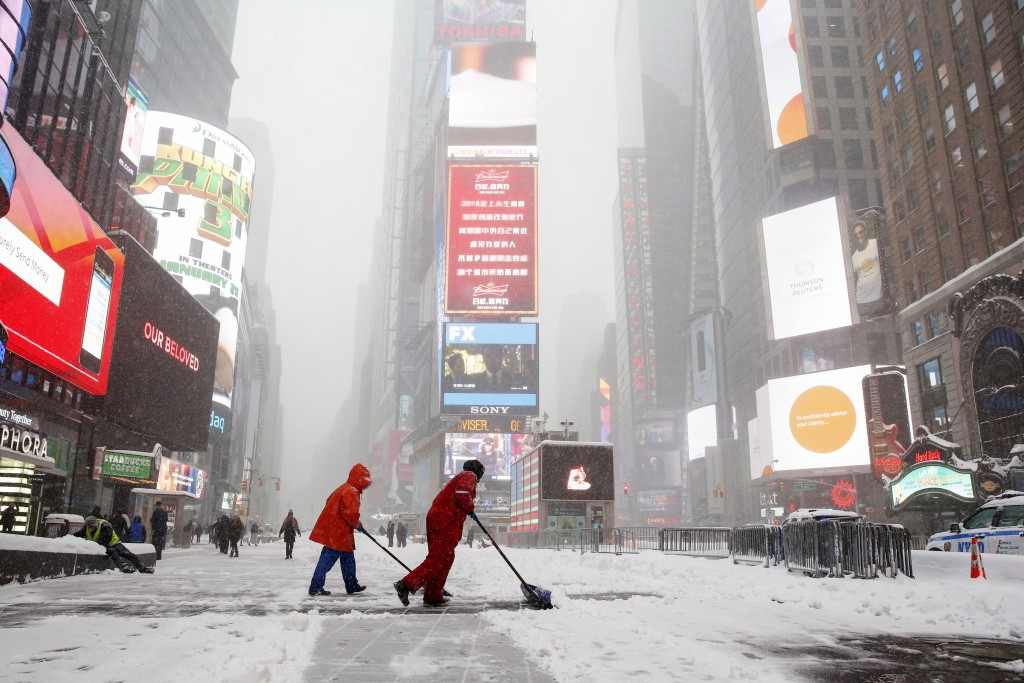 Workers shovel snow during a snowstorm at Times Square in the Manhattan on Jan. 23, 2016. A winter storm dumped nearly 2 feet of snow on the suburbs of Washington, D.C., on Saturday before moving on to Philadelphia and New York, paralyzing road, rail and airline travel along the U.S. East Coast. Photos By Shannon Stapleton/Reuters