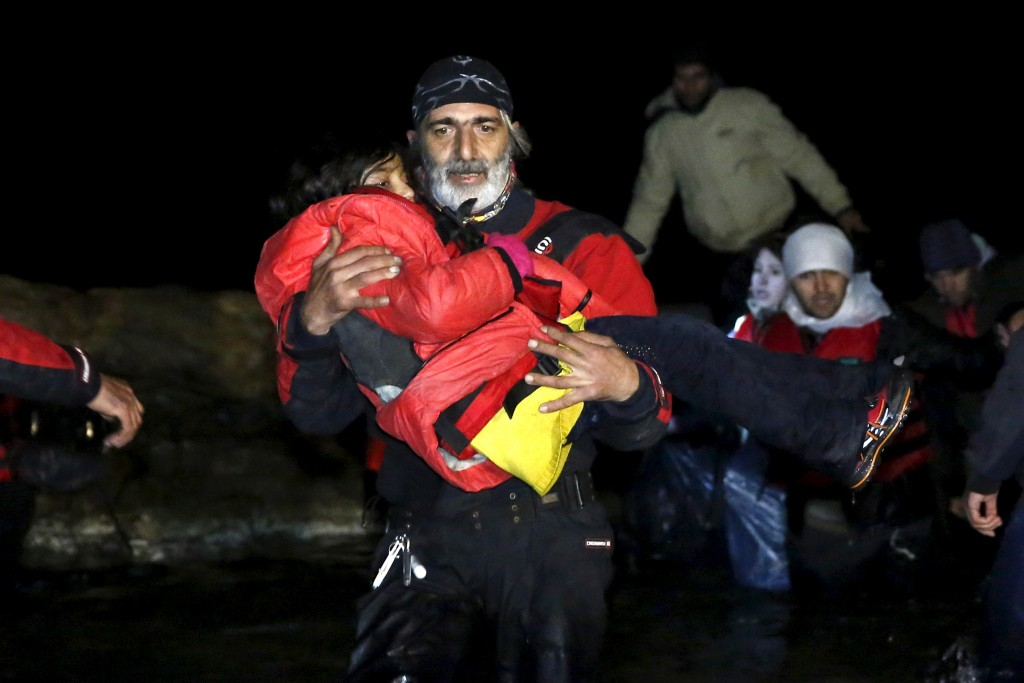 A volunteer carries a child as Afghan migrants arrive on a raft on the Greek island of Chios, early January 28, 2016. Giorgos Moutafis/Reuters