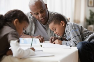 Grandfather watching grandchildren do homework. Photo illustration by Getty Images
