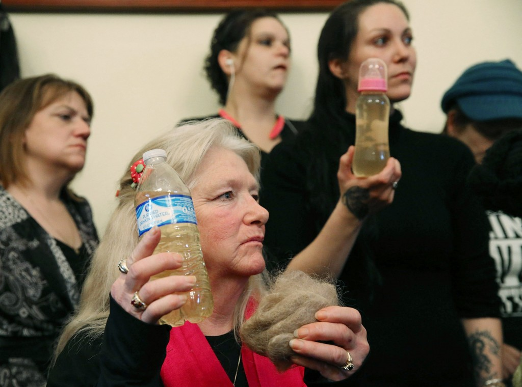 Flint residents Gladyes Williamson, center, holds a bottle of contaminated water, and a clump of her hair during a news conference after attending a House Oversight and Government Reform Committee hearing on the Flint, Michigan, water crisis in February 2016. Photo by Mark Wilson/Getty Images