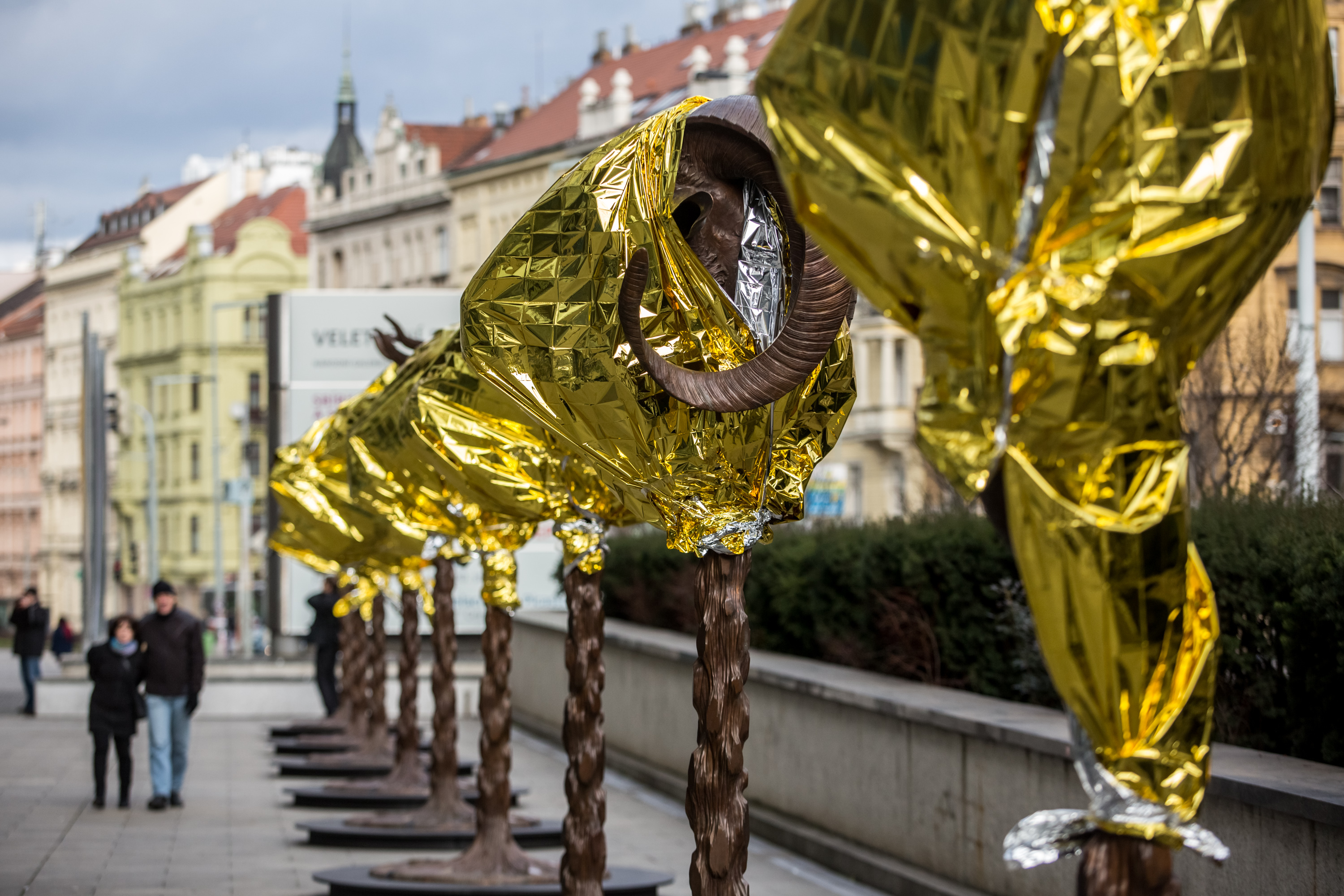 PRAGUE, CZECH REPUBLIC - FEBRUARY 05:  People walk past the 'Circle of Animals / Zodiac Heads' sculptures by Chinese artist Ai Weiwei in front of the Trade Fair Palace run by the National Gallery on February 5, 2016 in Prague, Czech Republic. An exhibition in front of the palace runs from February 6 to August 31, 2016. Ai Weiwei wrapped his bronze heads with thermal blankets to protest against migrants situation in Europe. It is the first time that the artist exhibits his work in the Czech Republic.  (Photo by Matej Divizna/Getty Images)