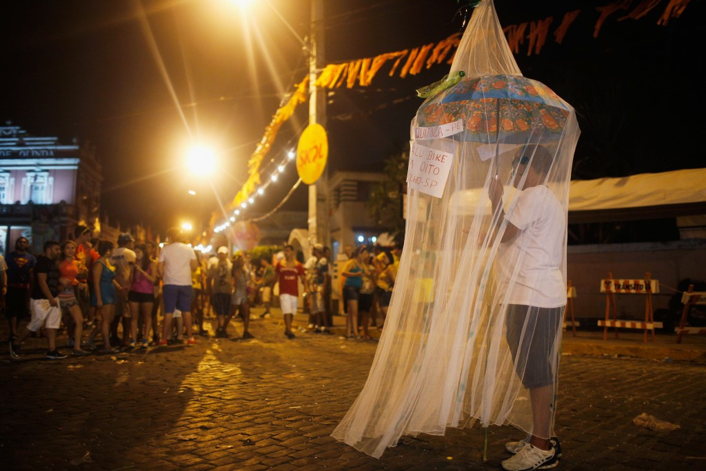 OLINDA, BRAZIL - FEBRUARY 06: A reveller stands beneath a mosquito net, as a satirical costume, during Carnival celebrations on February 6, 2016 in Olinda, Pernambuco state, Brazil. Revellers in Olinda and sister city Recife are gathering for various concerts and street parades during Carnival in spite of fears over the Zika virus. (Photo by Mario Tama/Getty Images)