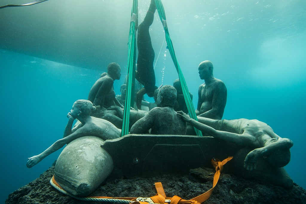 """""""The Raft of Lampedusa"""" is lowered to the ocean floor. Photo by Jason deCaires Taylor"""