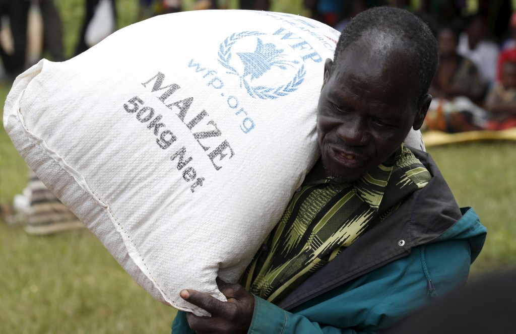 A Malawian man carries food aid distributed by the United Nations World Food Progamme (WFP) in Mzumazi village near the capital Lilongwe. A prototypical Malawi diet consists of corn, legumes, vegetables, and fruit, which  is insufficient for healthy growth on its own. Photo by Mike Hutchings/REUTERS