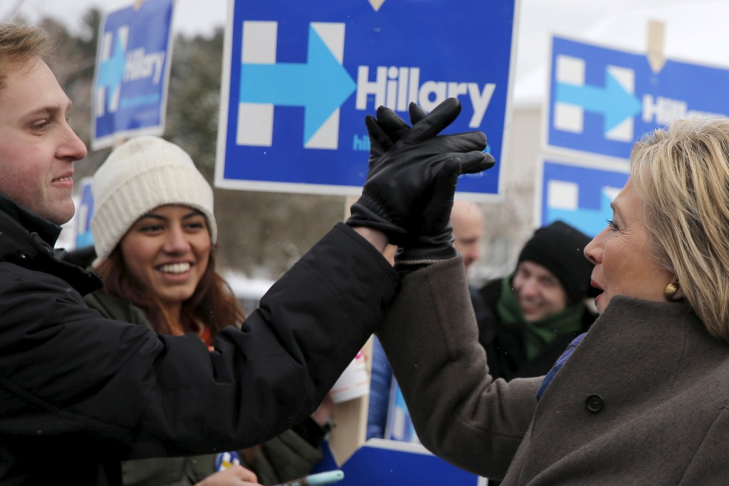 Hillary Clinton high-fives a supporter outside a polling place in Derry, New Hampshire on February 9, 2016, the day of New Hampshire's first-in-the-nation primary. Photo by REUTERS/Brian Snyder