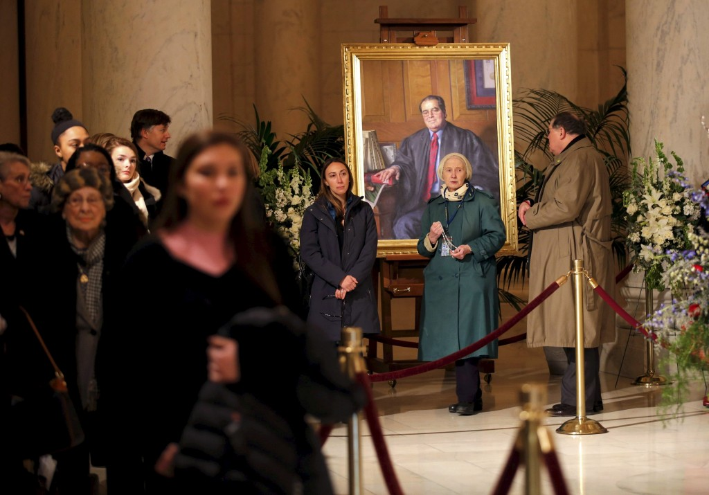 Members of the public stand next to a portrait of the late U.S. Supreme Court Justice Antonin Scalia while filing in to view his casket as it lies in repose in the Great Hall of the Supreme Court in Washington February 19, 2016. Scalia died on February 13, 2016 at the age of 79.   REUTERS/Carlos Barria        EDITORIAL USE ONLY. NO RESALES. NO ARCHIVE - RTX27PVC