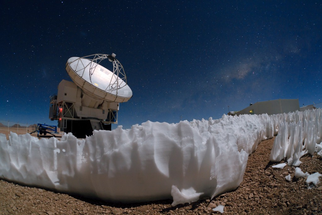 The Atacama Pathfinder Experiment (APEX) telescope is one of the tools used by European Southern Observatory to peer beyond the realm of visible light. Clusters of white penitentes -- thin spikes of hardened snow or ice --  can be seen in the foreground. Photo by ESO Photo Ambassador  Babak Tafreshi