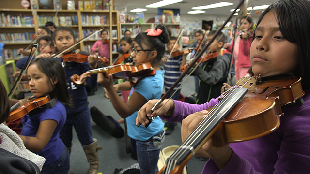Young violinists learn how to hold their instruments and bows. Photo by Greg Davis, courtesy of KCTS.