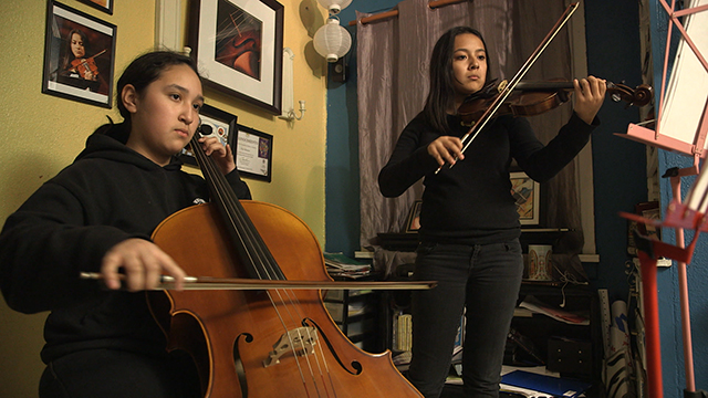 Flor Mateos' daughters practice their instruments at home. Photo by Greg Davis, courtesy of KCTS.