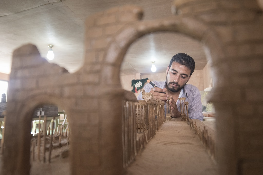 "Mahmoud built his model of Palmyra using clay and wooden kebab skewers. Mahmoud, who like the other artists is also from Dara'a, hopes that by seeing the exhibition, residents at Za'atari will remain connected with the country and culture they have been forced to leave behind.  ""This is a way for them not to forget. As artists we have an important role to play. A lot of what we know about ancient civilisations or prehistoric people is preserved through their art – Egyptian hieroglyphs or cave paintings."" Photo © UNHCR/Christopher Herwig"
