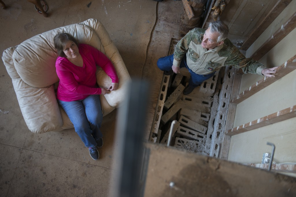 Sandra Landra and husband Gary stands where their fireplace used to be before the earthquake caused it to crumble in Prague, Oklahoma on January 25, 2015.  On November 5th, 2011 an intraplate earthquake measuring a record 5.7 occured near Prague.  The quake caused a 28-foot tall stone fireplace inside the Landra's A-frame home to collapse and rain down on Sandra who was relaxing in the living room.  She was taken to the emergency room and was badly bruised with 12 stitches. Photo by Linda Davidson / The Washington Post via Getty Images