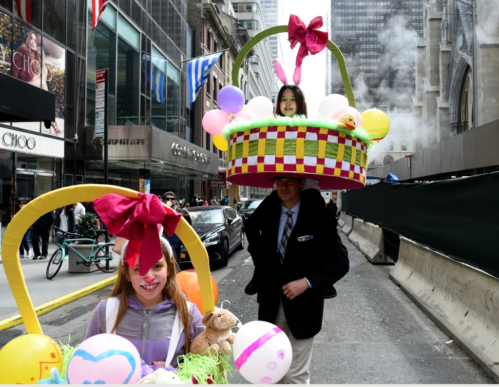 People on Fifth Avenue during the annual Easter Parade and Easter Bonnet Festival March 27, 2016 in New York.   The Easter Parade is a New York tradition that dates back to the middle of the 1800s. The social elite would attend services at one of the 5th Avenue churches and parade their new fashions down the Avenue afterwards. The flamboyant headgear and costumes are paraded down the Avenue to the delight of onlookers.  / AFP / Timothy A. CLARY        (Photo credit should read TIMOTHY A. CLARY/AFP/Getty Images)