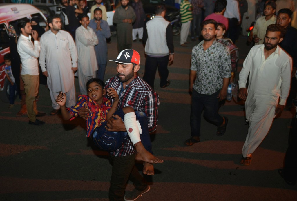 A Pakistani relative carries an injured child to the hospital in Lahore on March 27, 2016, after at least 56 people were killed and more than 200 injured when an apparent suicide bomb ripped through the parking lot of a crowded park in the Pakistani city of Lahore where Christians were celebrating Easter. / AFP / ARIF ALI        (Photo credit should read ARIF ALI/AFP/Getty Images)