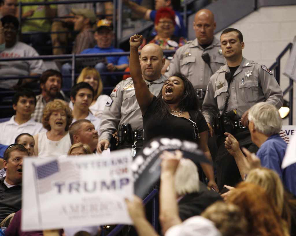 A black demonstrator raises her fist in protest against U.S. Republican presidential candidate Donald Trump as police officers approach to remove her from a campaign rally in Fayetteville, North Carolina March 9, 2016. Photo by Jonathan Drake/Reuters.