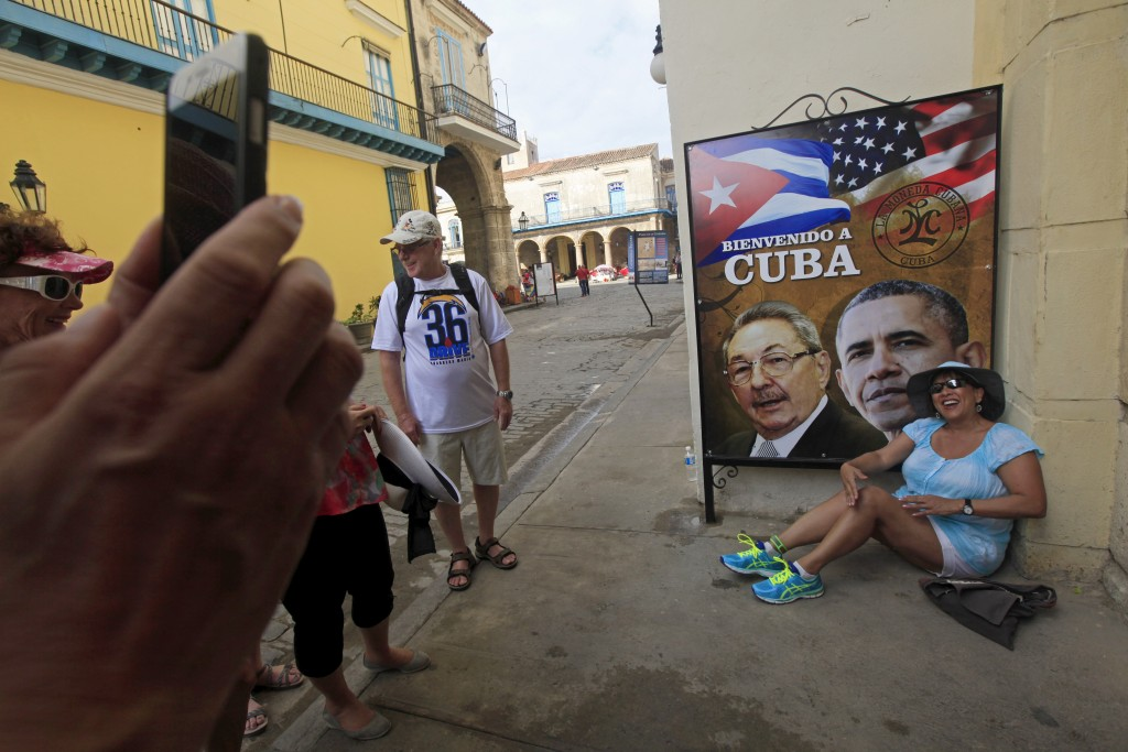 A visitor from California has her picture taken by a travel companian next to images of Cuba's President Raul Castro and U.S. President Barack Obama in Havana, Cuba March 19, 2016. Photo by Reuters.