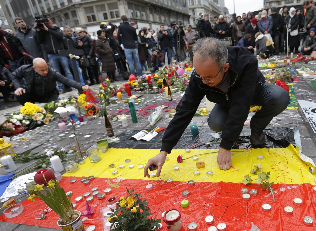 People place candles on a street memorial following Tuesday's bomb attacks in Brussels, Belgium, on March 23. Photo by Francois Lenoir/Reuters