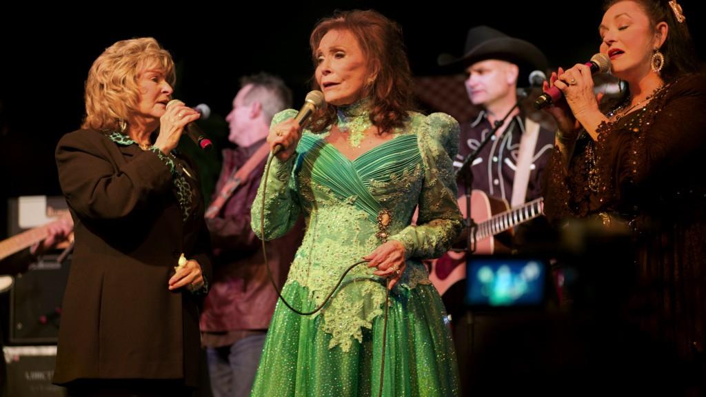 "Loretta Lynn (C) performs with her sisters Peggy Sue Wright (L) and Crystal Gayle (R) in ""American Masters: Loretta Lynn: Still a Mountain Girl."" Image provided by Elliott Halpern/Yap Films Inc."