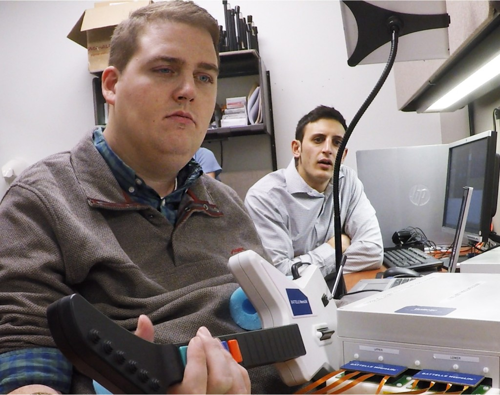 Nick Annetta, right, of Battelle, watches as Ian Burkhart, 24, plays a guitar video game using his paralyzed hand. A computer chip in Burkhart`s brain reads his thoughts, decodes them, then sends signals to a sleeve on his arm, that allows him to move his hand. Photo by Ohio State University Wexner Medical Center/ Batelle