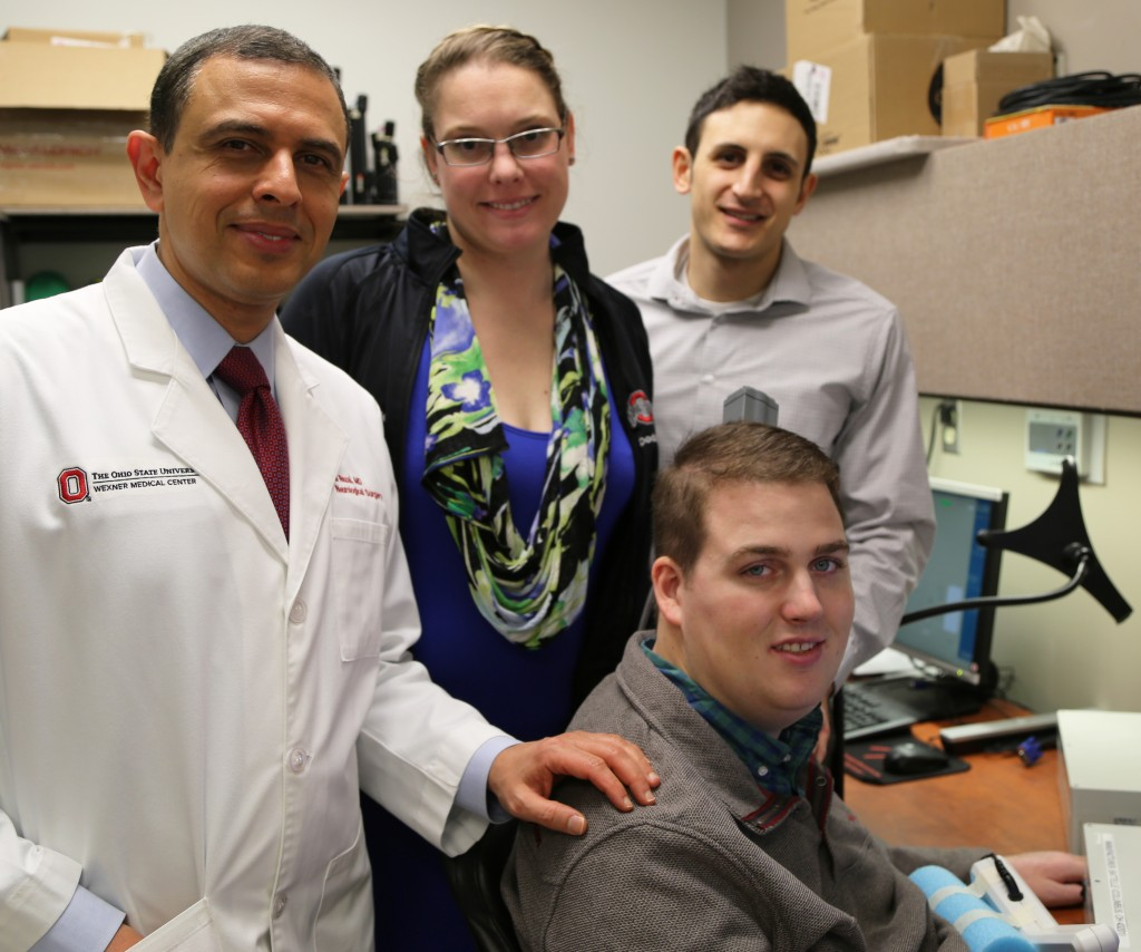 Patient Ian Burkhart, seated, poses with members of the research team (from left) Dr. Ali Rezai and Dr. Marcie Bockbrader of The Ohio State University Wexner Medical Center and Nick Annetta of Battelle during a neural bypass training session. Photo by Ohio State University Wexner Medical Center/ Batelle