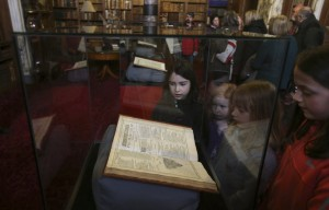 Children look at one of the three leather-bound volumes of Shakespeare's First Folio, discovered nearly 400 years after his death. Image by Russell Cheyne / REUTERS