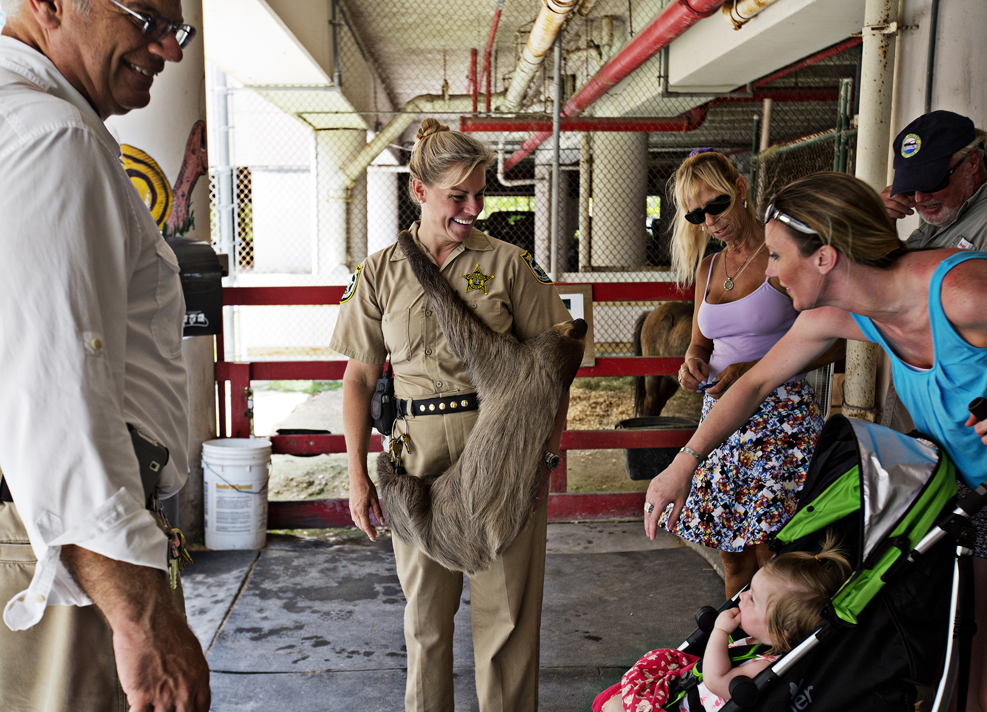 "Curator Jeanne Selander - ""Farmer Jeanne"" - holds ""Mo"" the sloth, and visits with a crowd of visitors for an open house at the jail farm. ""Everyone thinks he is hugging me, but really he just thinks I'm a tree,"" says Selander.  Photo by Kim Raff"