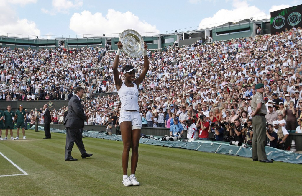 Venus Williams of the U.S. holds the trophy after winning the final against France's Marion Bartoli at the Wimbledon tennis championships in 2007. That same year, Wimbledon became the last Grand Slam event to offer equal pay after Venus Williams and other female players pressured organizers that ran the tournament. Photo by Toby Melville/Reuters