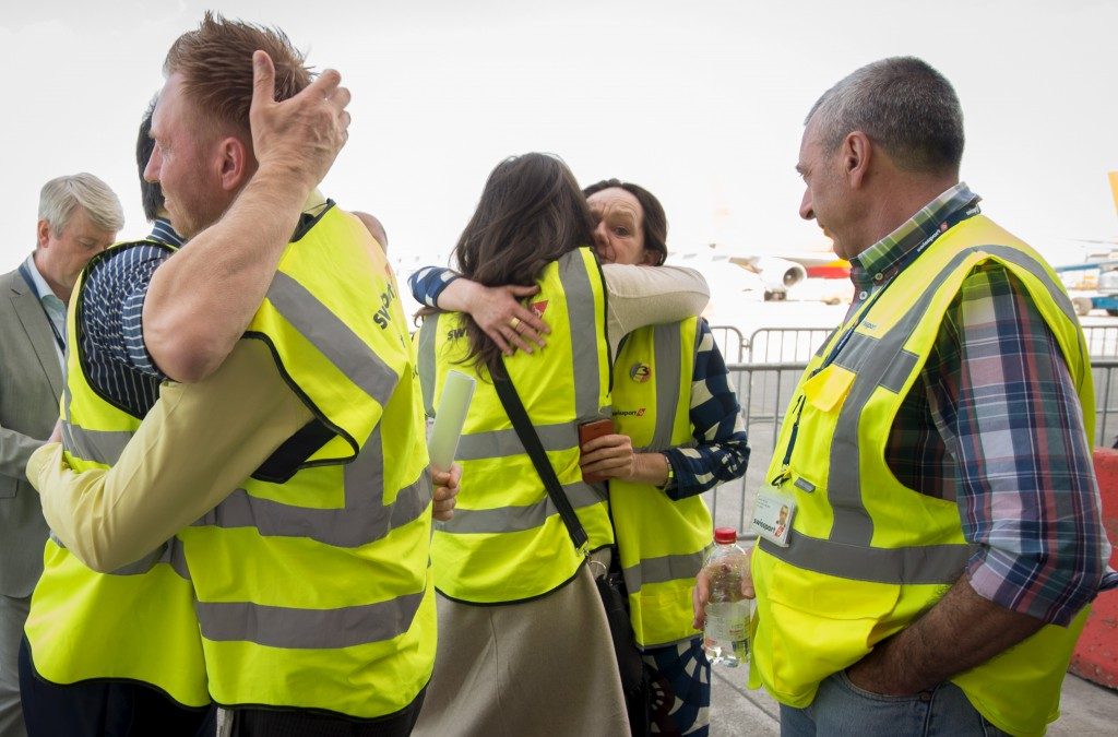 Brussels Airport staff hug as the first plane takes off from Brussels Airport, which partially re-opened following a bomb blast 12 days ago, in Zaventem, Belgium April 3, 2016. Benoit Doppagne/Reuters