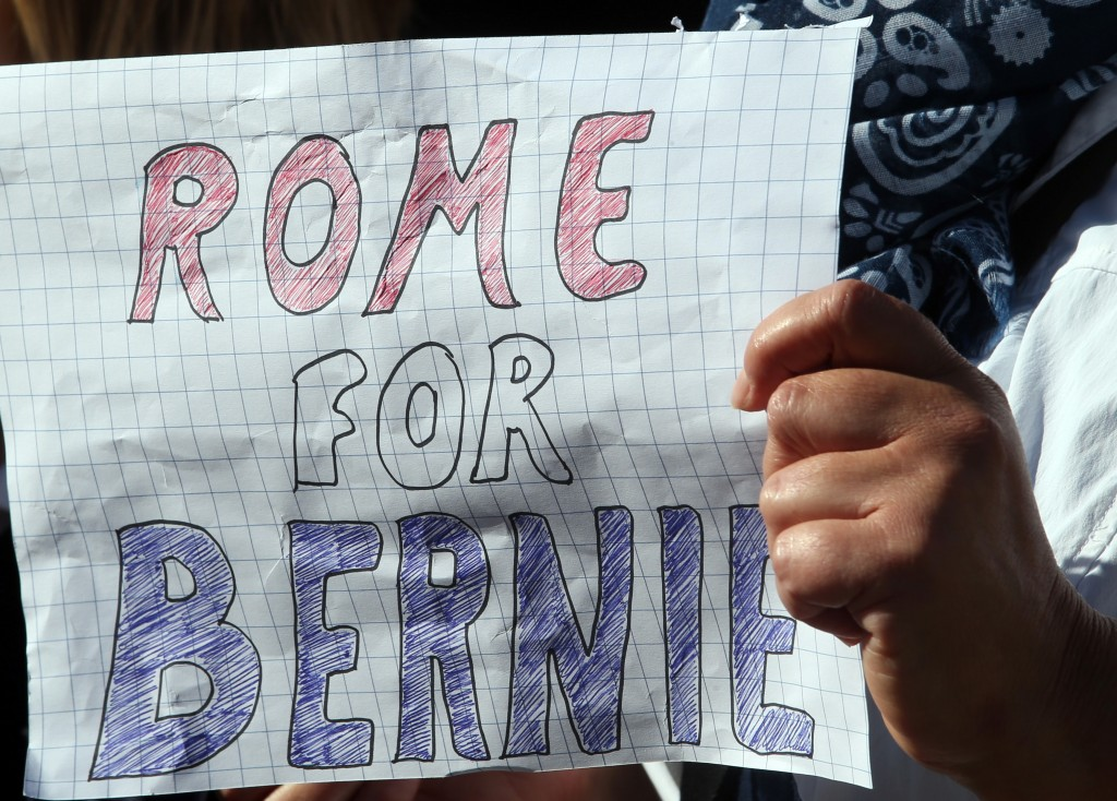 A supporter of Democratic presidential candidate Bernie Sanders holds a welcome sign at the Vatican. Photo by Stefano Rellandini/Reuters