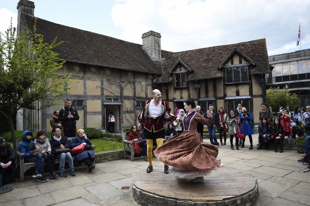 Tourists watch actors perform at the house where William Shakespeare was born during celebrations to mark the 400th anniversary of the playwright's death in Stratford-Upon-Avon, Britain, April 23, 2016. REUTERS/Dylan Martinez - RTX2BBGQ
