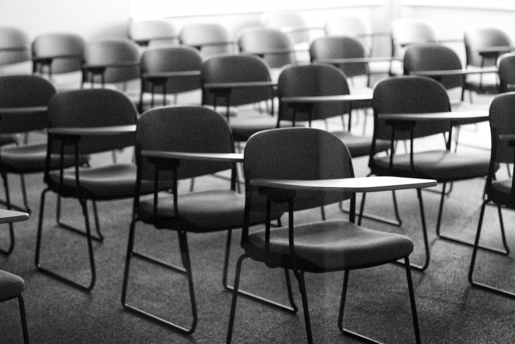 Rows of desks sit empty in a classroom. Photo by Alan Levine/Flickr