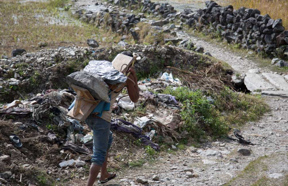 A man carries stones to a project site in Eastern Nepal. Photo by Mark Rikkers of the dZi Foundation