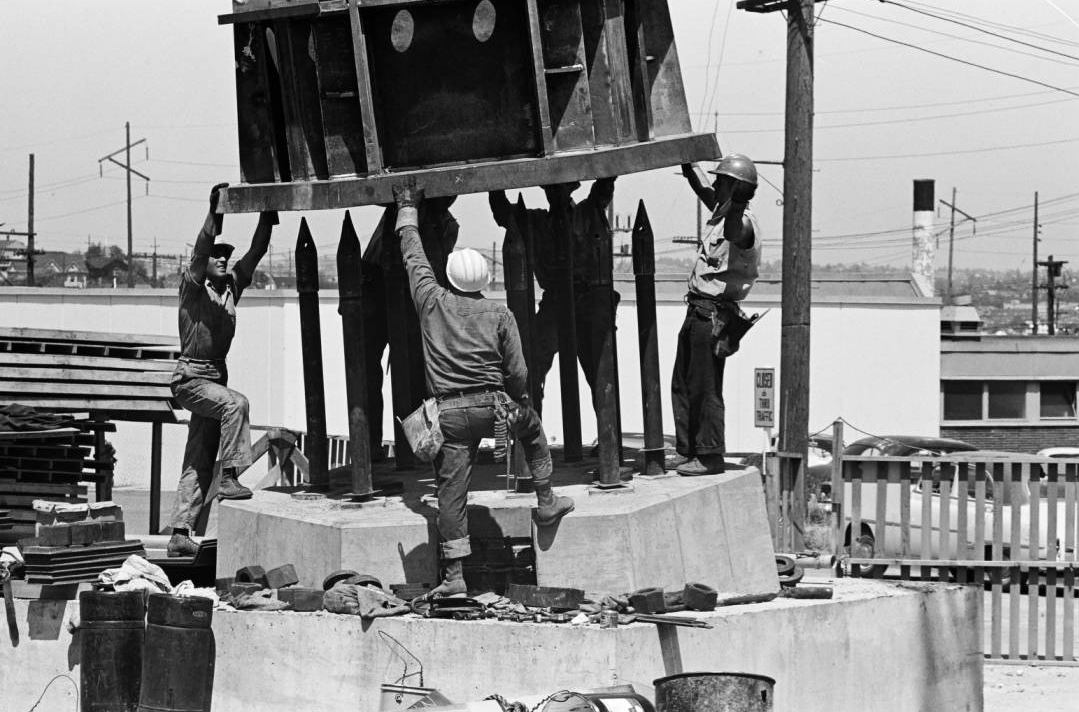 Workers guiding base of Space Needle leg into place, ca. June 30, 1961. Workers preparing ground for Space Needle foundation, ca. April 1961. Photo by by George Gulacsik, image courtesy of the Seattle Public Library