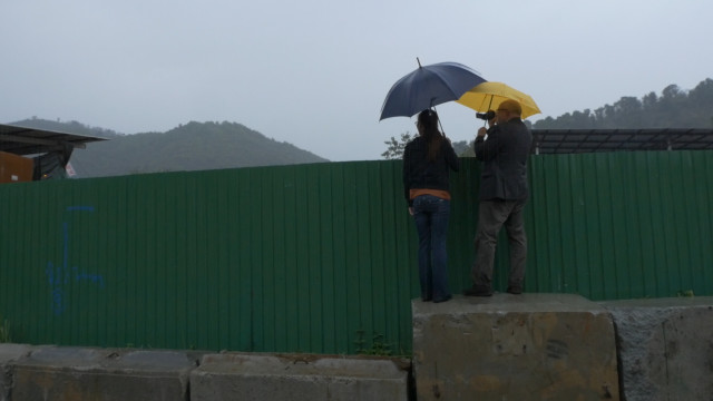Dongxia Su and Jim Puckett peek over the fence of an e-waste scrapyard in the New Territories of Hong Kong. Photo by Ken Christensen, KCTS9/EarthFix