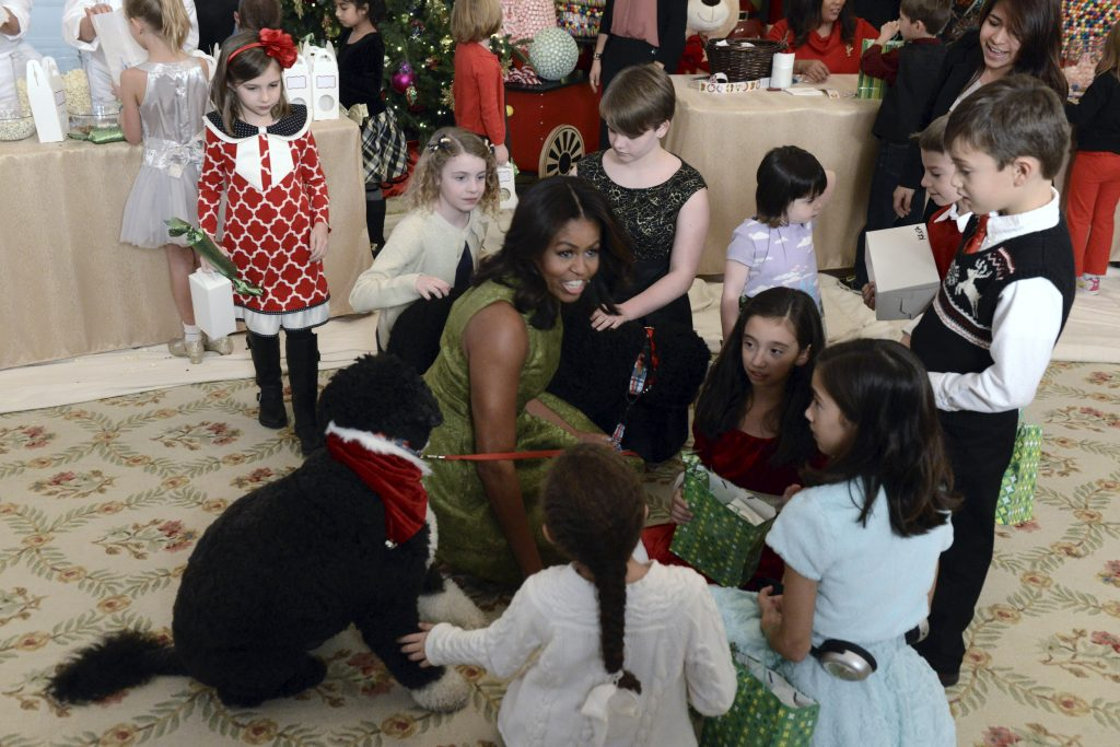First Lady Michelle Obama (C) chats with children of military families as they gather to see the pets Bo and Sunny and enjoy holiday decorations and treats at the White House, in Washington, December 2, 2015. Photo By Mike Theiler/Reuters