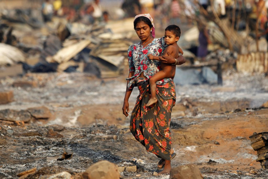 A woman carrying a baby walks among debris after fire destroyed shelters at a camp for internally displaced Rohingya Muslims in the western Rakhine State near Sittwe, Myanmar May 3, 2016. Photo By Soe Zeya Tun/Reuters