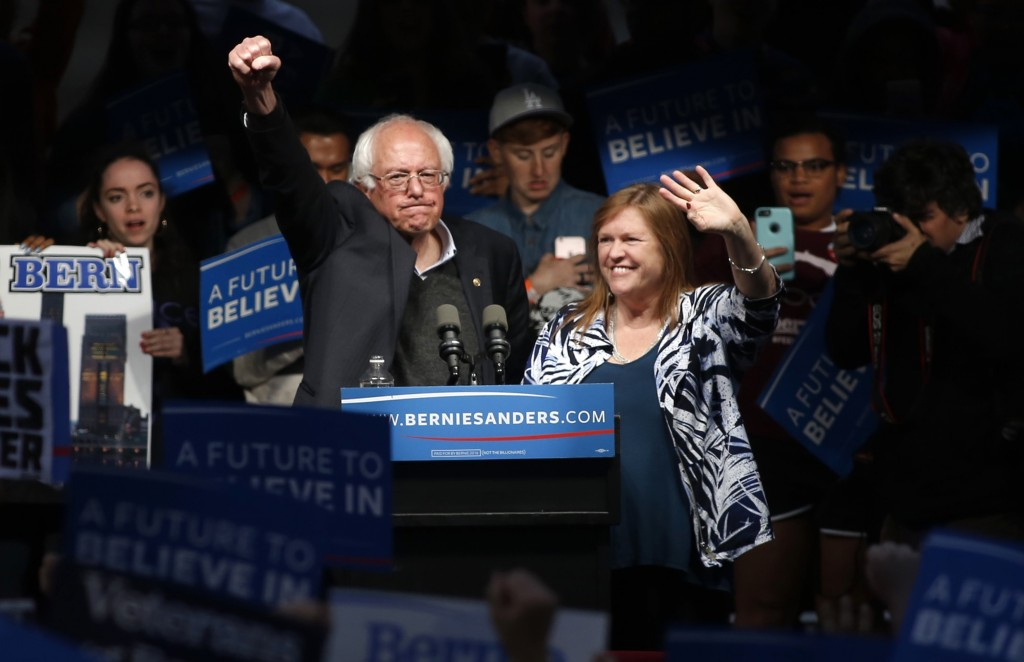 Democratic U.S. presidential candidate and U.S. Senator Bernie Sanders pumps his first in the air to the crowd after his wife Jane (R) came onstage and whispered in his ear as he spoke to supporters at a campaign event held during Indiana primary day at Waterfront Park in Louisville, Kentucky, U.S., May 3, 2016. REUTERS/Aaron P. Bernstein - RTX2CPEH