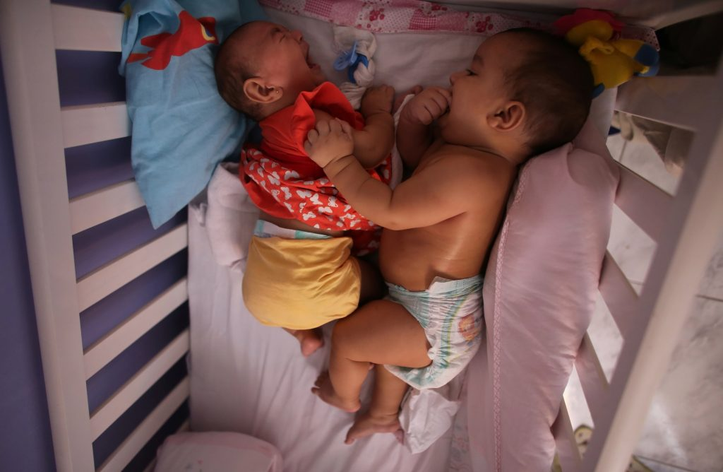 Five-month-old twins, Laura (L) and Lucas lie in their bed at their house in Santos, Sao Paulo state, Brazil April 20, 2016. Among the mysteries facing doctors in Brazil battling an epidemic of the little-known Zika virus are cases of women giving birth to twins with only one suffering from microcephaly, a birth defect associated with the disease. Photo by Nacho Doce/REUTERS