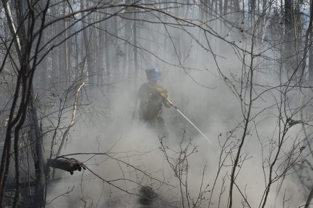 A member of Wildfire Management Alberta's Wild Mountain Unit out of Hinton, hoses down hotspots in the Parsons Creek area of Fort McMurray, Alberta, Canada, May 6, 2016. Picture taken May 6, 2016. Chris Schwarz/Government of Alberta/Handout via Reuters ATTENTION EDITORS - THIS IMAGE WAS PROVIDED BY A THIRD PARTY. EDITORIAL USE ONLY. FOR EDITORIAL USE ONLY. NOT FOR SALE FOR MARKETING OR ADVERTISING CAMPAIGNS. THIS IMAGE HAS BEEN SUPPLIED BY A THIRD PARTY. IT IS DISTRIBUTED, EXACTLY AS RECEIVED BY REUTERS, AS A SERVICE TO CLIENTS - RTX2D9H1