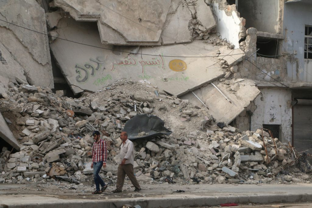 "Men walk near a damaged building in Aleppo's rebel held al-Fardous district, Syria May 26, 2016. The graffiti reads in Arabic reads:"" Smile to (anger) your enemy"". Photo By Abdalrhman Ismail/Reuters"