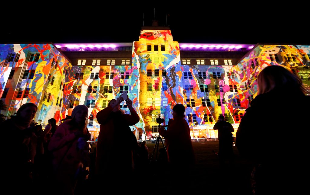 People take pictures of a design projected onto the Museum of Contemporary Art during the opening night of the annual Vivid Sydney light festival in Sydney, Australia May 27, 2016. REUTERS/Jason Reed - RTX2EGAT