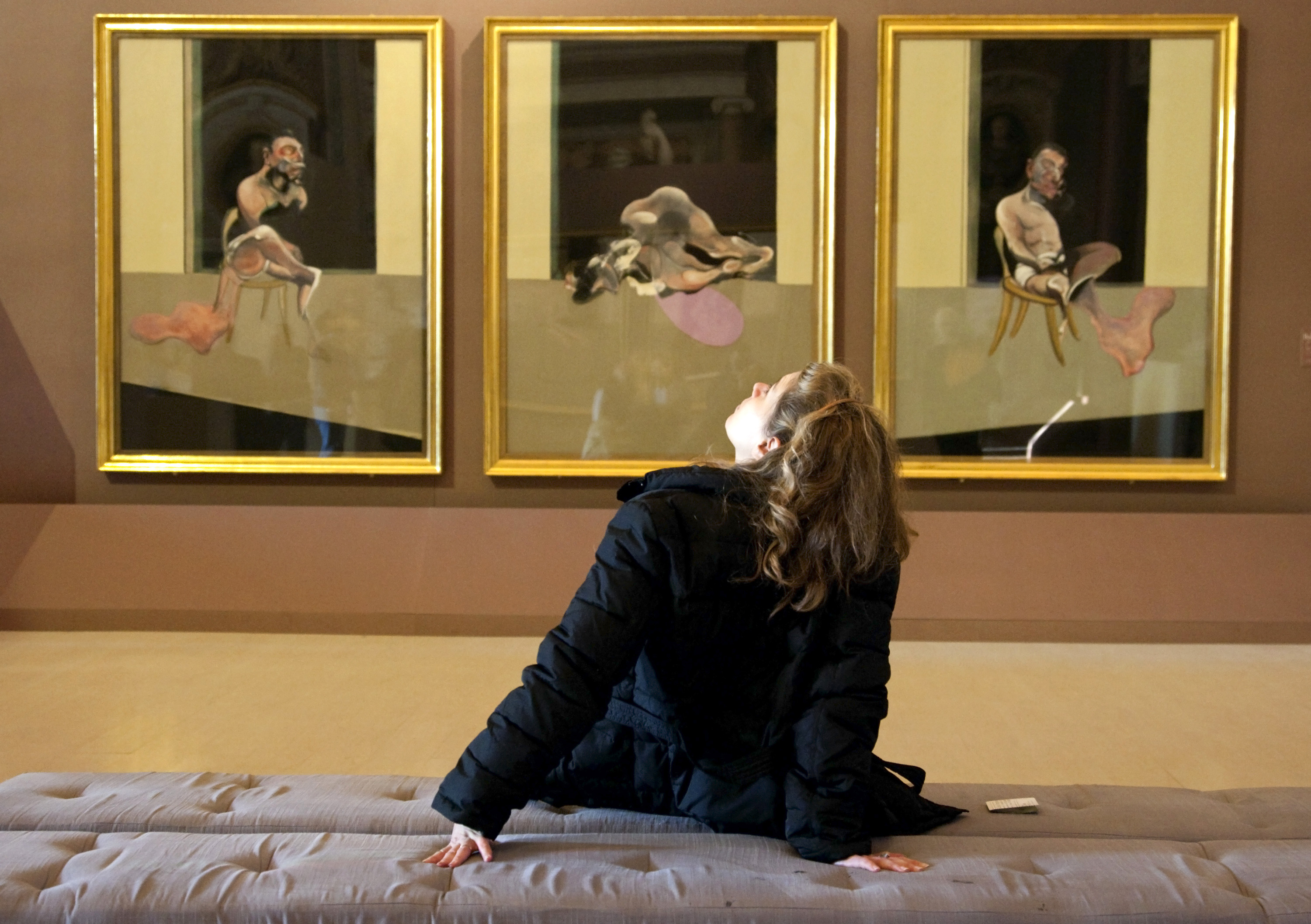 A woman looks at a Francis Bacon painting during an exhibition at the Galleria Borghese in Rome November 11, 2009. Portraits by Italian master Caravaggio and Irish-born 20th-century painter Francis Bacon stand side-by-side in new exhibition connecting their tormented views of humanity despite contrasting approaches to realism. The show at Rome's Galleria Borghese marks 400 years since Caravaggio's death and 100 years since Bacon's birth and at its heart lies their shared fascination with the human form and their predilection for the expressive portrait. Picture taken November 11, 2009. To match Reuters Life! ITALY-CARAVAGGIO/BACON            REUTERS/Max Rossi   (ITALY SOCIETY) - RTXQMYI