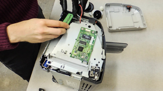 A Basel Action Network employee places a GPS tracker inside a broken printer. Courtesy of the Basel Action Network