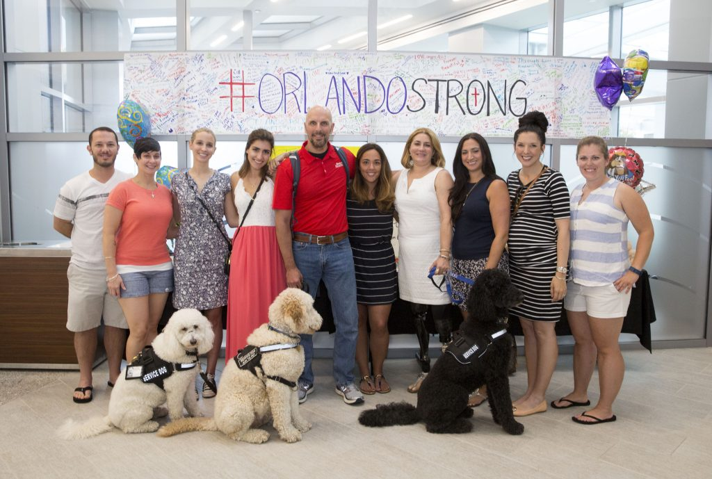Boston Marathon bombing survivors visit Orlando Regional Medical Center to meet with Pulse shooting survivors. From left: Nick Yanni, Lee Ann Yanni, Eliza Gedney, Sydney Corcoran, Dave Fortier, Nicole O'Neil, Celeste Corcoran, Sabrina Dello Russo, Michelle L'Heureux and Elizabeth Birmingham. Front row service dogs Koda, Zealand and Sebastian. Photo By Orlando Health