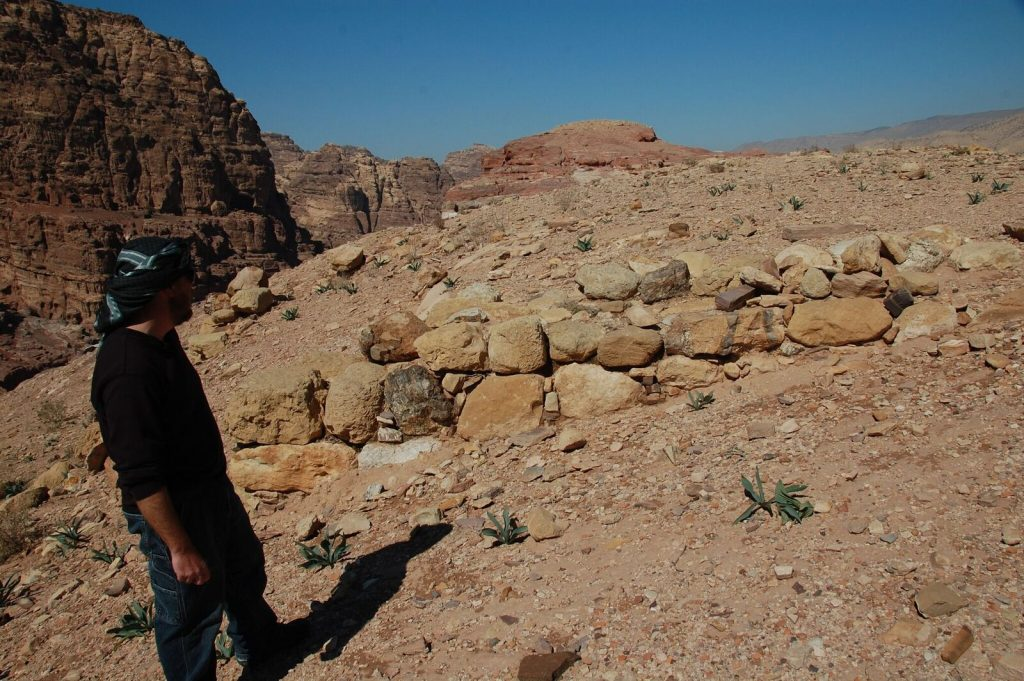 Archaeologist Christopher A. Tuttle examines a recently discovered site in the ancient Jordanian city of Petra. Photo by Q. Tweissi