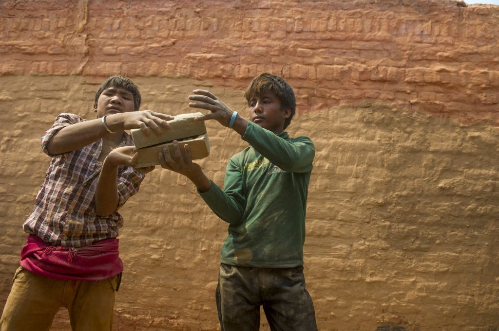 DHADING, NEPAL - APRIL 14: Young men and boys stack bricks inside a kiln on April 14, 2016 in Dharke Bazar in the Dhading district, Nepal. Despite a national law that bans children under the age of 14 from working, many work alongside their families in the country's brick making industry. Photo by Ann Hermes/The Christian Science Monitor
