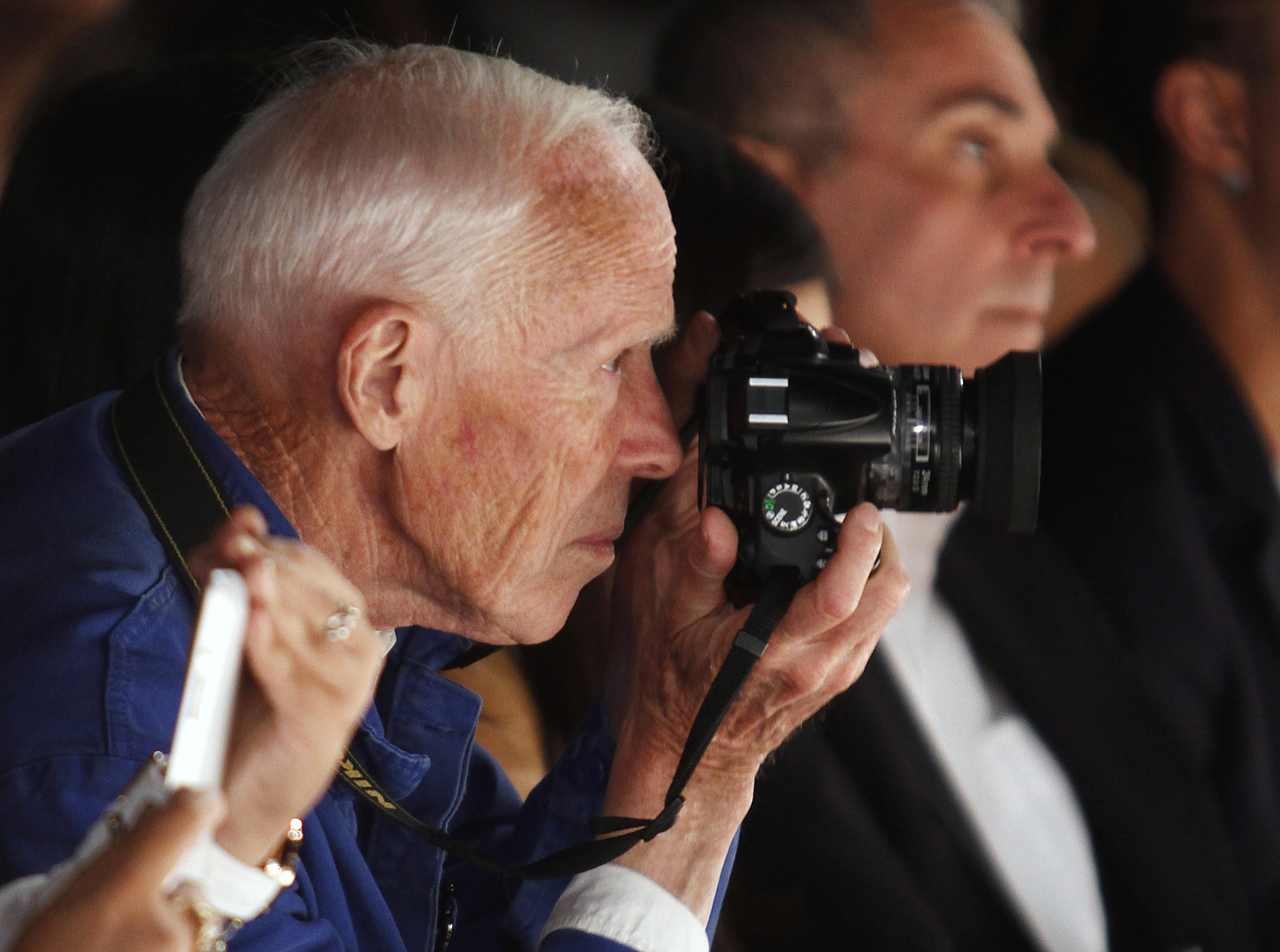 New York Times photographer Bill Cunningham takes photos during the Naeem Khan Spring/Summer 2013 collection show at New York Fashion Week September 11, 2012. REUTERS/Carlo Allegri (UNITED STATES - Tags: FASHION MEDIA) - RTR37UN0